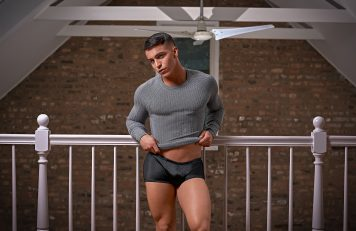 Man posing in a shirt and underwear by a railing