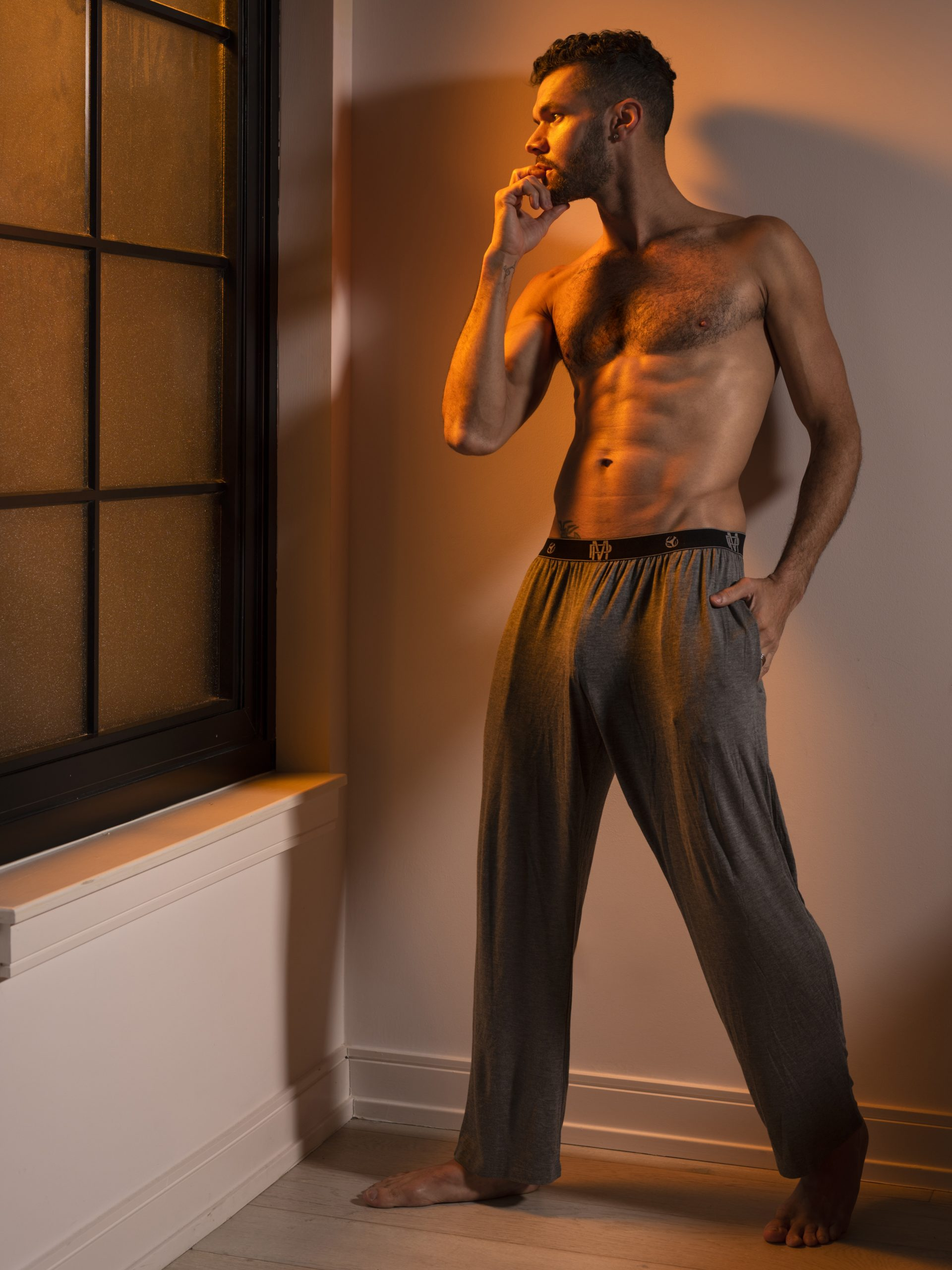 Man standing by the window in Male Power lounge pants