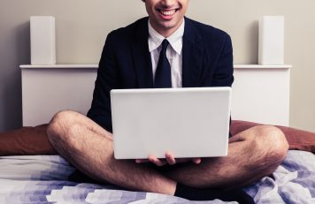 Man in a suit top and tie on his computer in bed with no pants on