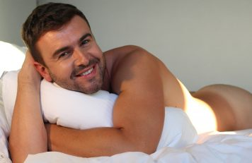 man naked in bed with a pillow